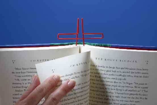 Just slip book clip above the pages while legs are still behind pages.  Turn your page and slip the bookclip back down!
